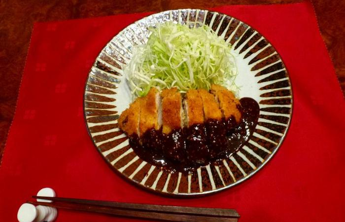 Tonkatsu fried pork cutlet with dark miso sauce on plate with pile of shredded cabbage
