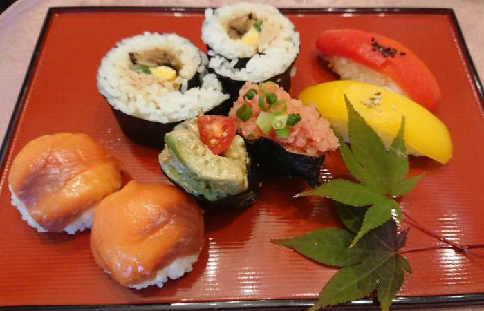 8 pieces of sushi (topped with red and yellow fish, rolled, topped with wasabi and roe) on red square plate with leaves