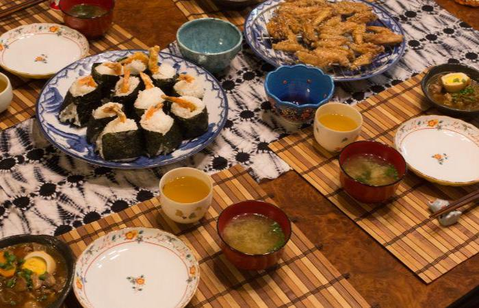 Tebasaki chicken wings and tenmusu tempura sushi spread on Japanese dishware with bowls of tea and miso
