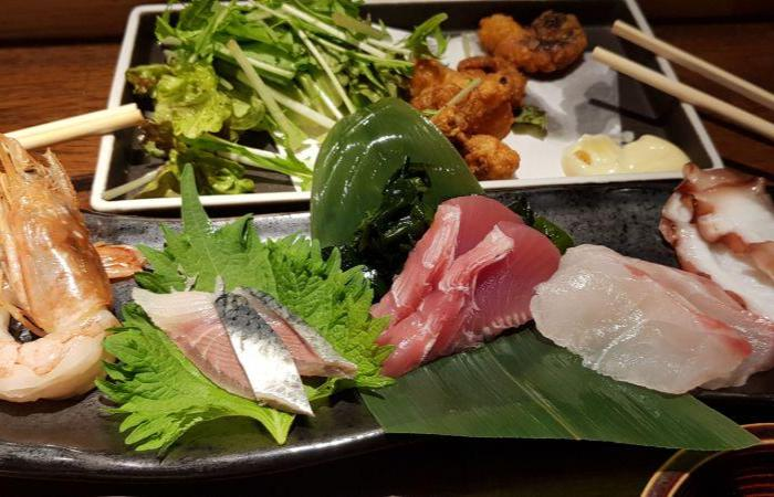 Several plates of meat, sashimi on green leaves, leafy vegetables