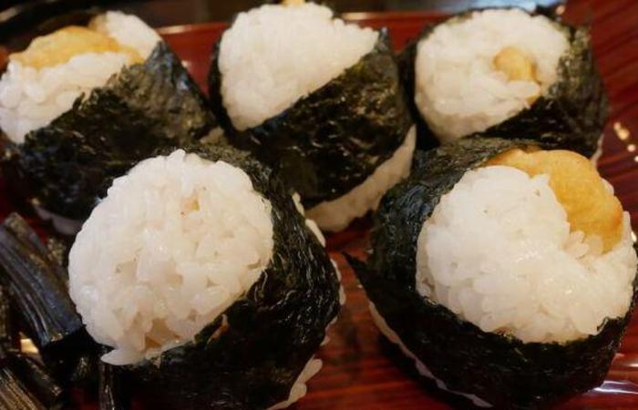 Five tenmusu rice balls with tempura shrimp inside on dish
