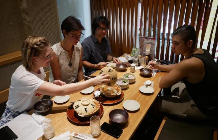 Travelers sat around table with dishes, one opening pot of miso nikomi udon
