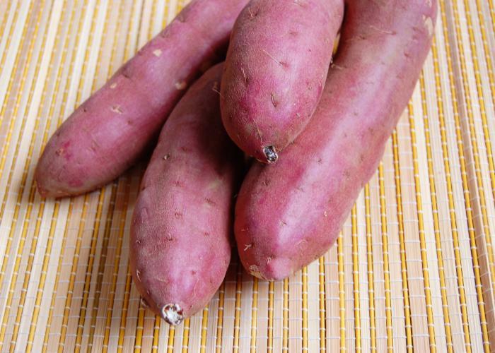 Four raw reddish-purple Satsuma-imo Kagoshima sweet potatoes on a light yellow mat