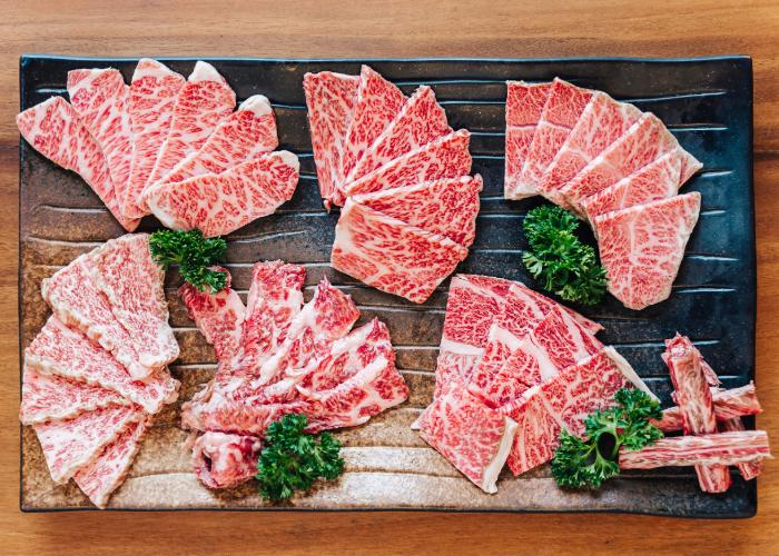 Slices of wagyu beef on a black stone tray